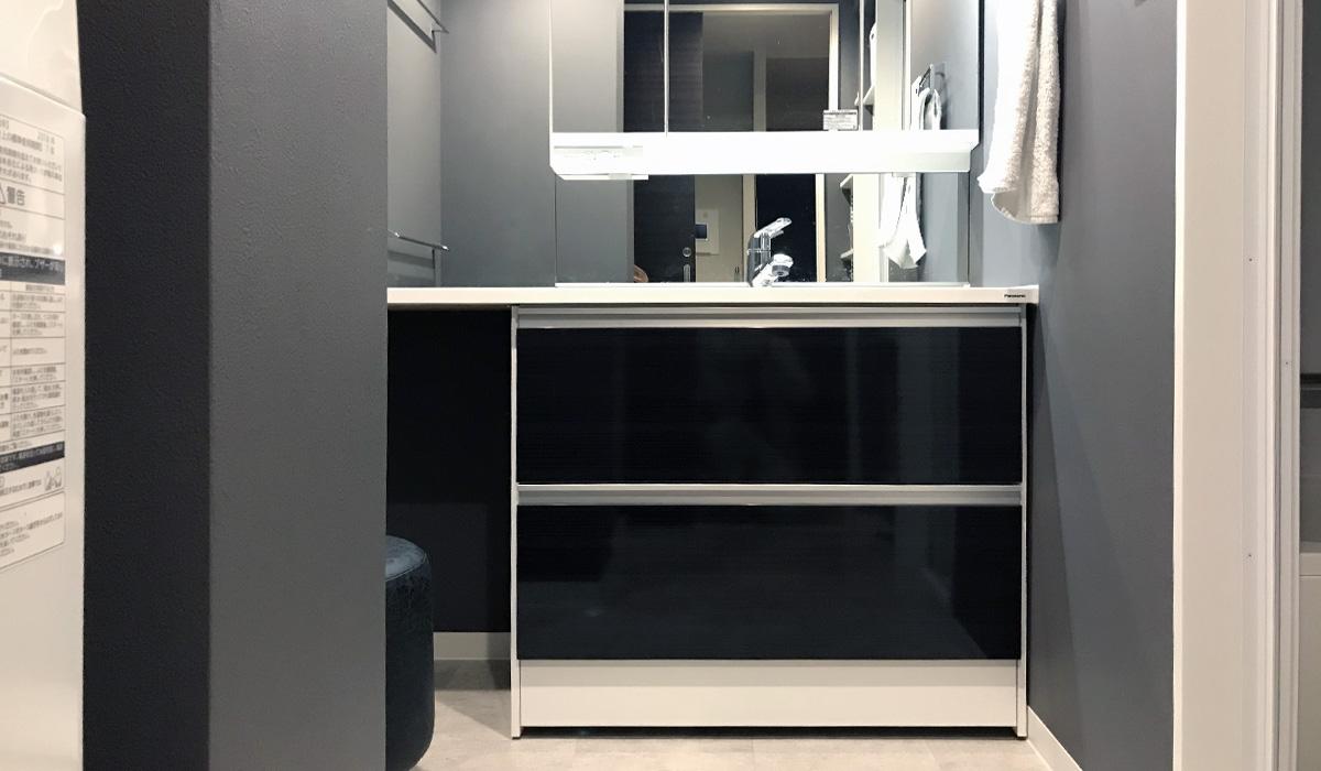 グレーの洗面所と黒い洗面台